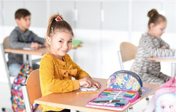Dziecko w szkole przy ławce